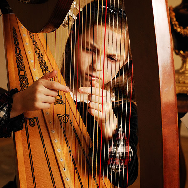 A young girl playing the harp