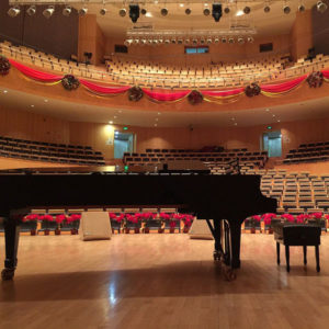 A piano in an empty concert hall