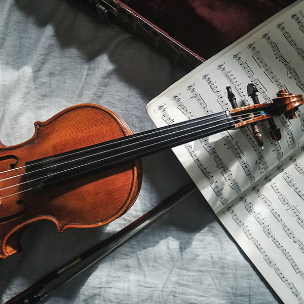 A violin and bow on top of sheet music